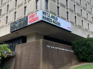 "LED banner outside of Vanderbilt's Central Library reading "" Don't Worry, We'll Hold Hands Again"""