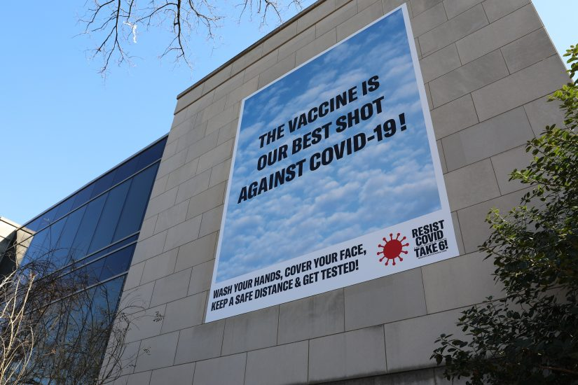 Banner on building reading The Vaccine is our Best Shot Against Covid-19