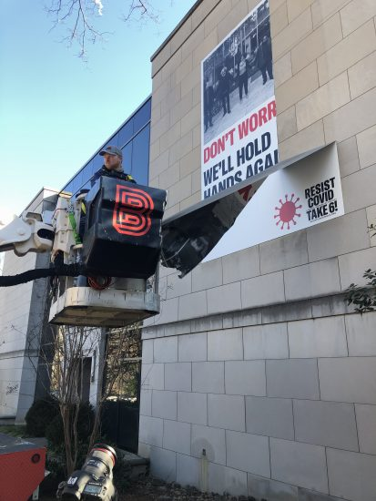 Covid-19 Banner being installed on building by man in bucket truck