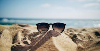 sunglasses sitting on sand